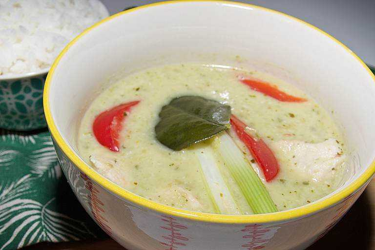 A traditional bowl of creamy, aromatic Thai green curry with chunks of chicken in a small bowl with jasmine rice.